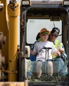 Child in heavy equipment with operator